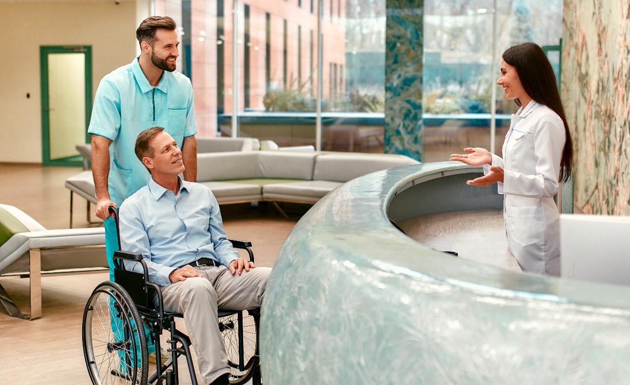 patient-in-wheelchair-talking-to-receptionist